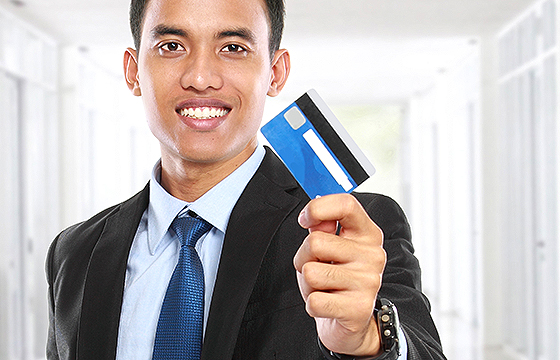 asian businessman holding credit or debit card