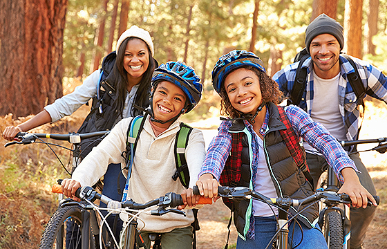 family of four smiling on bicycle ride