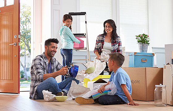 family of four unpacking in new home