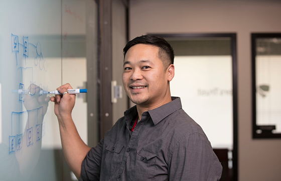 man smiling and writing on whiteboard